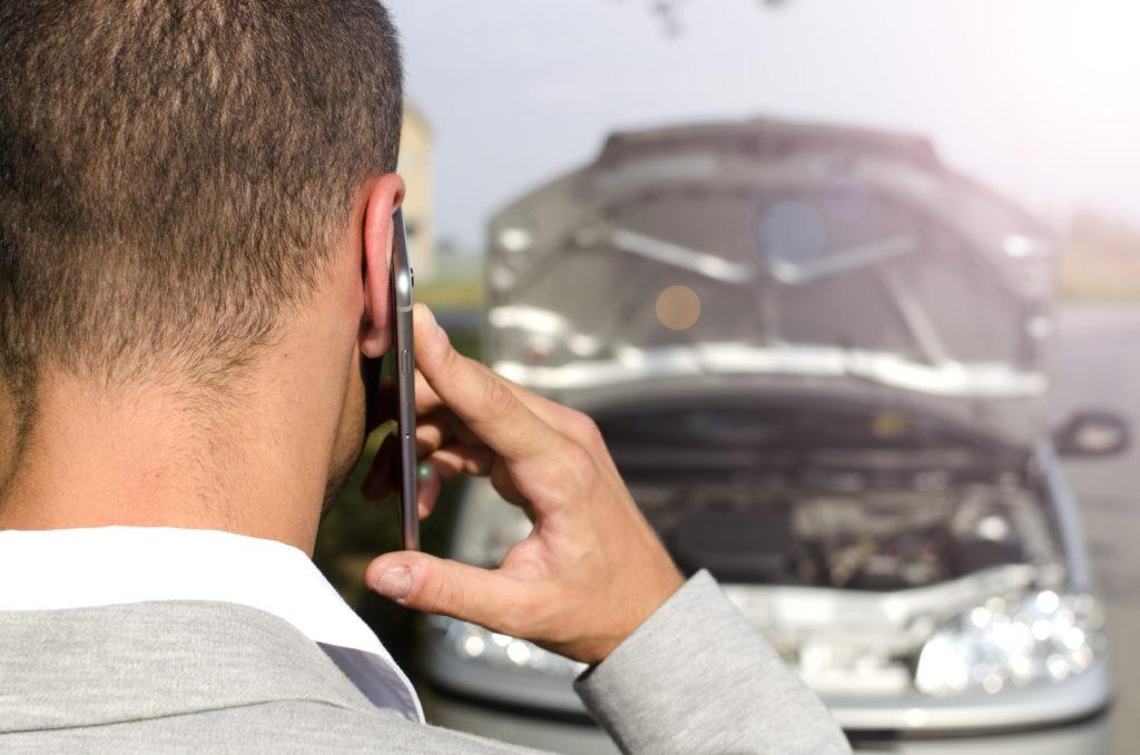 personne avec une voiture en panne contactant l'assistance