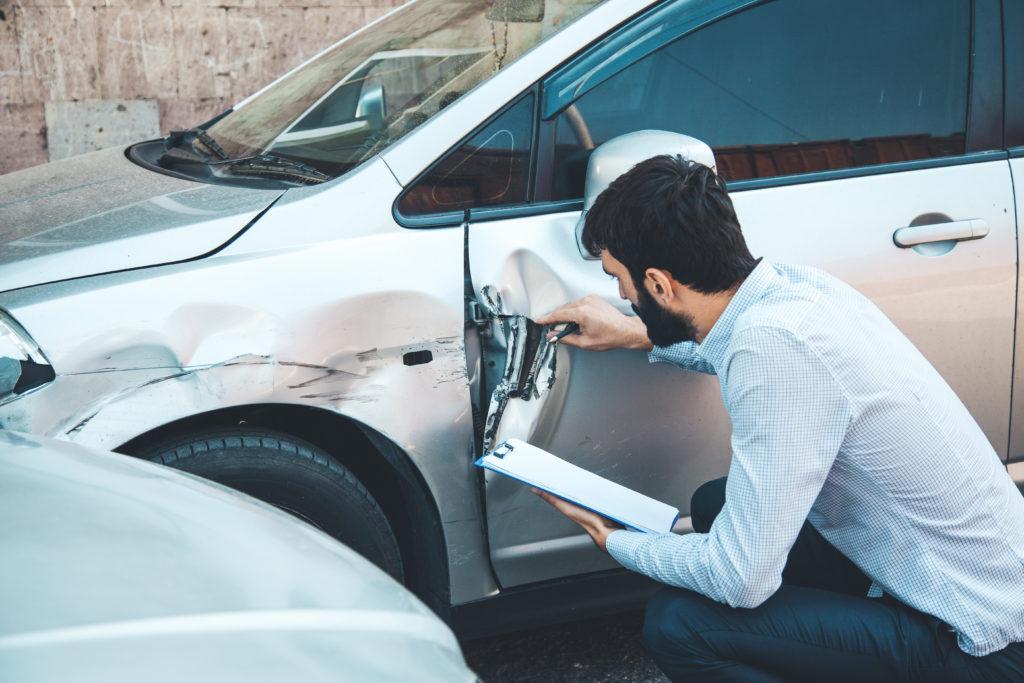 expert examinant une voiture accidentée