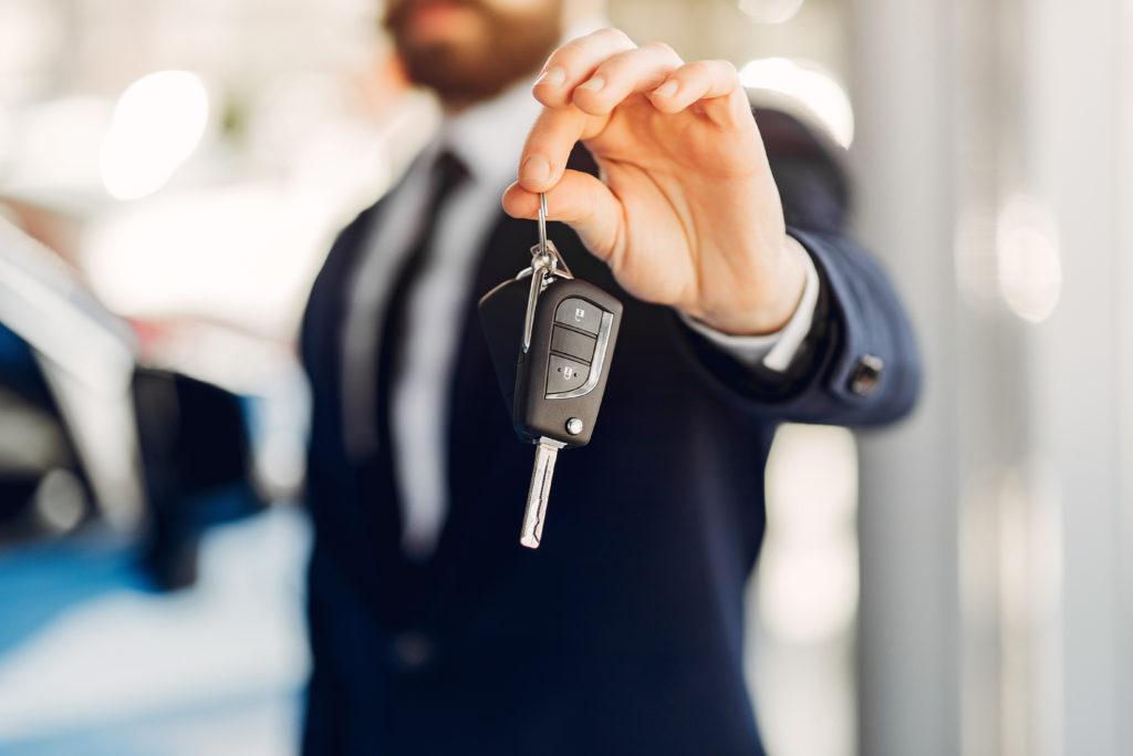 homme tendant les clés d'une voiture